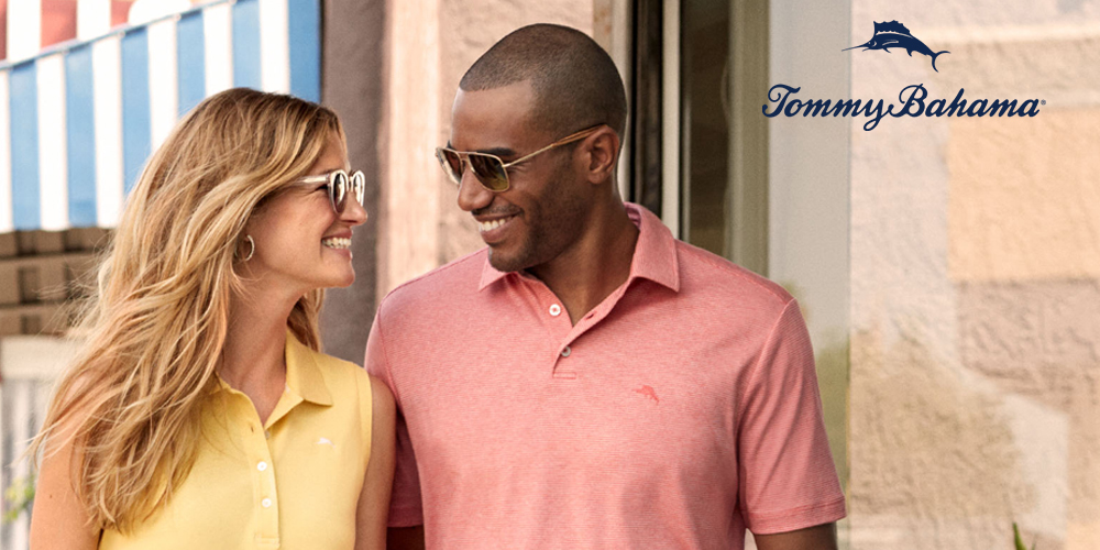 smiling blonde woman in a yellow shirt with african american man wearing a pink polo